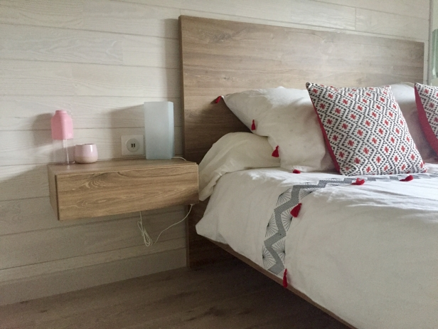 Détails du lit, table de chevet, parquet et pan de mur en bois par déco-mag